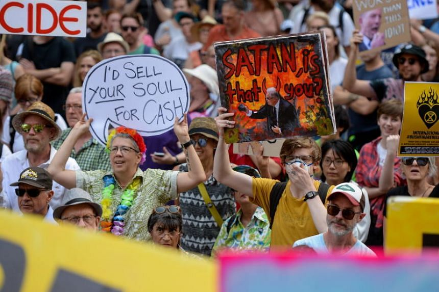 Protesters hold placards during a climate change rally under the slogan 'Sack ScoMo!' in Sydney, on Jan 10, 2020, as bushfires burn across the country.