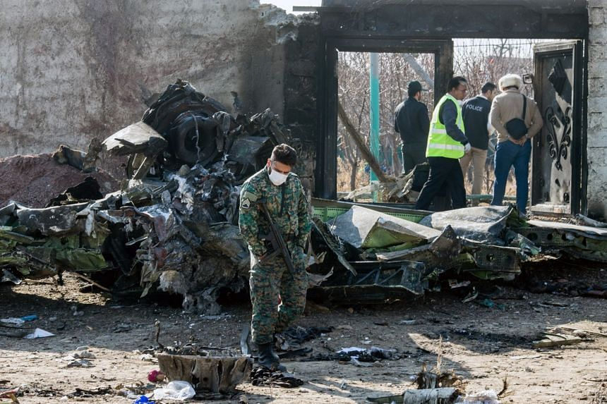A security official examines a piece of wreckage at the site of the Ukraine International Airlines crash, Jan 8, 2020.
