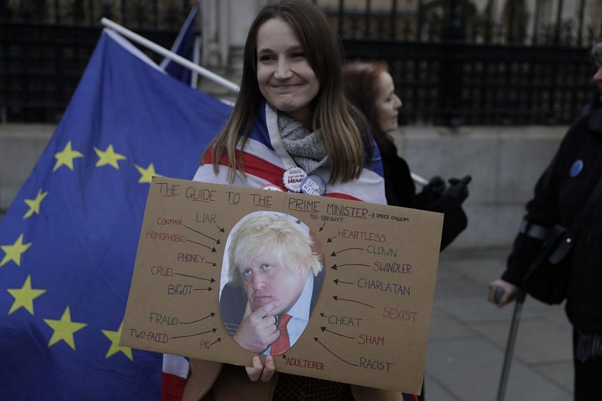 An anti-Brexit protester holds a placard depicting British Prime Minister Boris Johnson as she demonstrates outside the Houses of Parliament in London.