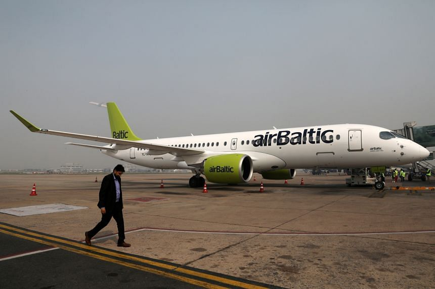 A man walks past an airBaltic Airbus A220-300 aircraft at Indira Gandhi International Airport in India on Nov 12, 2019.
