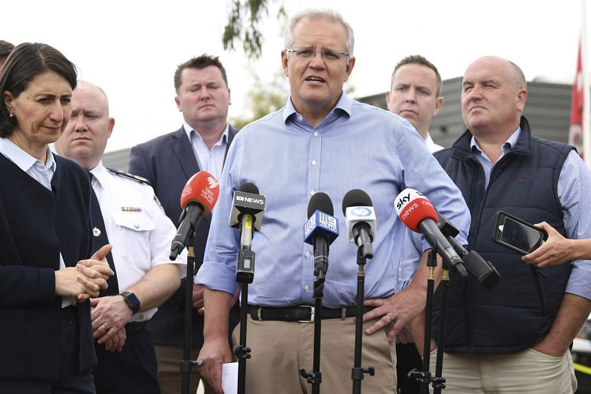 Australia's Prime Minister Scott Morrison (centre), with NSW Premier Gladys Berejiklian (left) speaks to the media during a visit to the Wollondilly Emergency Control Centre in Sydney, on Dec 22, 2019.