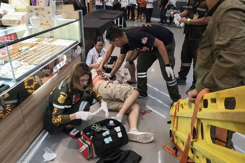 Paramedics helping a man who was wounded during a robbery at the Robinson shopping mall in the town of Lopburi, north of Bangkok, on Jan 9, 2020.