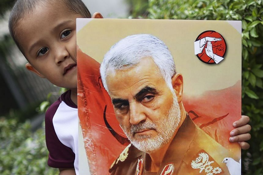 A child holds a portrait of slain general Qasem Soleiman during a Peace No War demonstration in Kuala Lumpur, Malaysia.