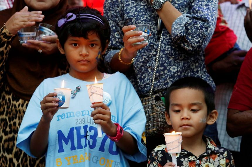 A March 2019 photo shows Iman and Muhammad, children of MH370 flight attendant Mohd Hazrin Hasnan, hold candles during a remembrance event in Kuala Lumpur.