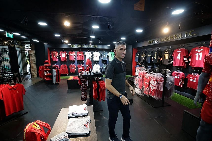 Liverpool ambassador Luis Garcia taking a tour of the club's official merchandise store at Bugis Junction yesterday. The club also have three stores in Thailand, and will open branches in Dubai and Vietnam next week. ST PHOTO: KEVIN LIM