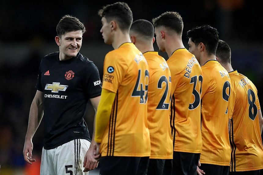 Manchester United centre-back Harry Maguire (left) eyeing up the Wolves defence during their goal-less FA Cup third round match last Saturday. He has since been out with a hip injury but could face Norwich today. PHOTO: REUTERS