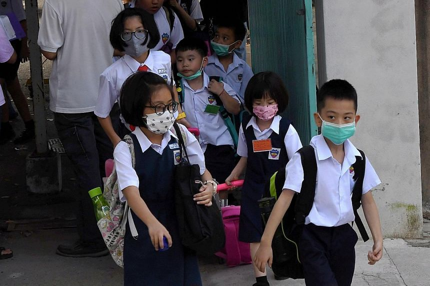 Pupils at the Chinese language school SJKC Li Hwa in Malaysia wearing face masks on Thursday. Nineteen pupils in two classes at the school came down with the flu on Thursday. PHOTO: BERNAMA