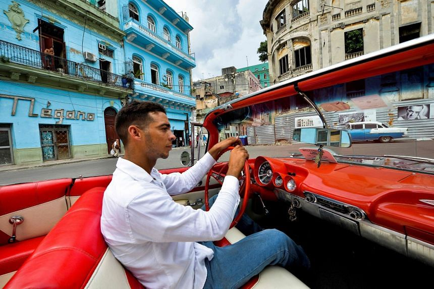 Cuban Yosbel Sosa, 33, drives his 1959 Chevrolet Impala through the streets of Havana, in search of tourists.