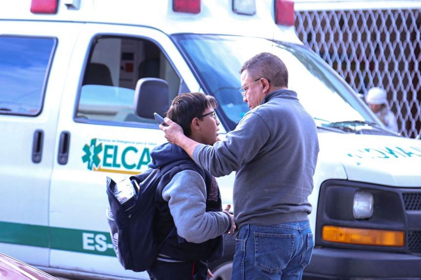 A man and his son are seen outside the elementary school in Mexico where an 11-year-old boy shot and killed his teacher and wounded six other people before killing himself.