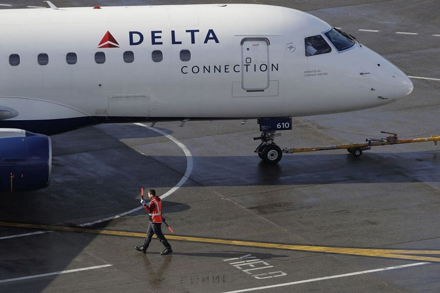 A February 2019 photo shows a ramp worker guiding a Delta Air Lines plane at Seattle-Tacoma International Airport.