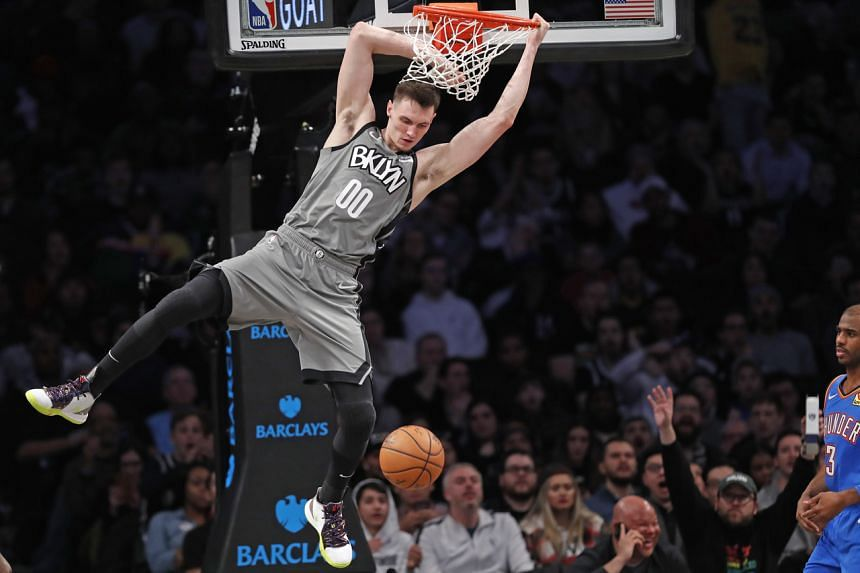 Brooklyn Nets forward Rodions Kurucs hangs from the rim after dunking a ball during an NBA basketball game against the Oklahoma City Thunder on Jan 7, 2020, in New York.