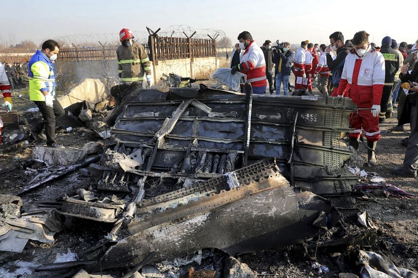 Rescue workers search the scene where a Ukraine International Airlines plane crashed near Teheran on Jan 8, 2020.