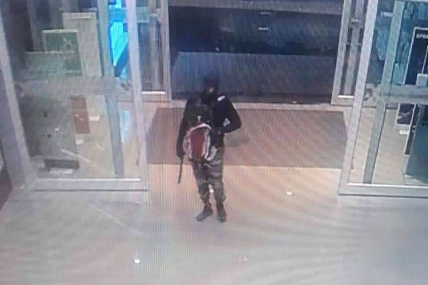 A series of CCTV screen grabs shows a gunman as he enters the Robinson shopping mall, approaches a counter, and then jumps onto it in Lopburi province, Thailand, on Thursday. ,