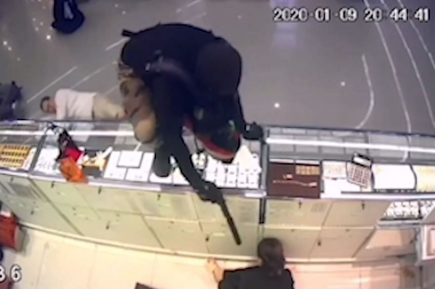 A series of CCTV screen grabs shows a gunman as he enters the Robinson shopping mall, approaches a counter, and then jumps onto it in Lopburi province, Thailand, on Thursday.