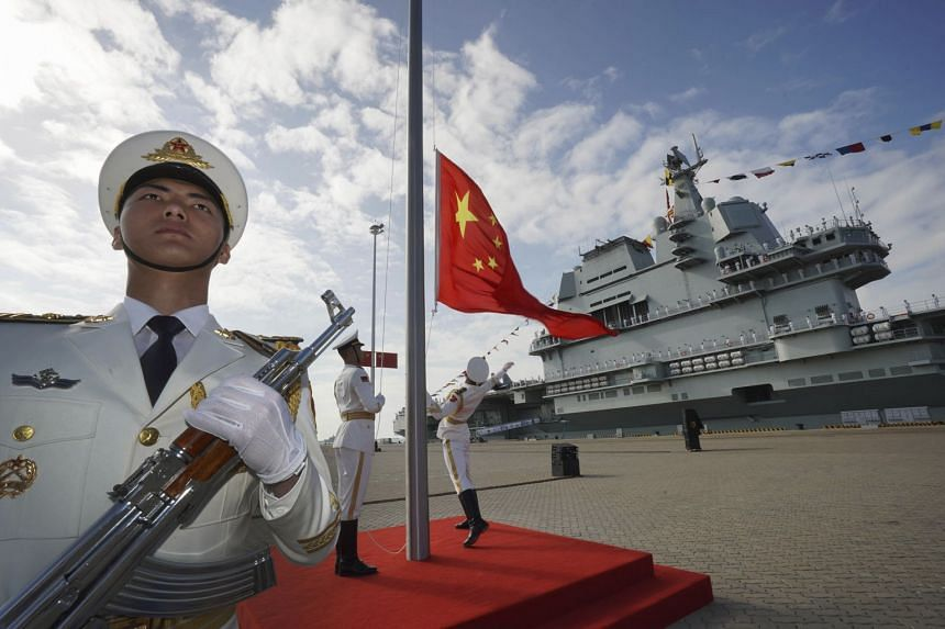 A December 2019 photo shows a Chinese honour guard raising the Chinese flag during a commissioning ceremony for China's Shandong aircraft carrier.
