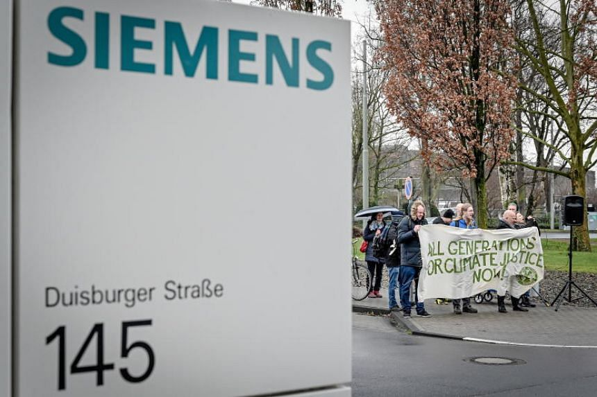 Activists protest in front of the administration building of Siemens Mobility in Krefeld-Uerdingen, Germany, on Jan 10, 2020.