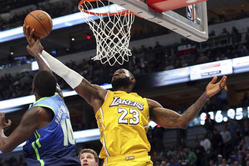 Dallas Mavericks forward Dorian Finney-Smith (left) tries to defend against a shot by Los Angeles Lakers forward LeBron James during the second half in the game between the Dallas Mavericks and Los Angeles Lakers.