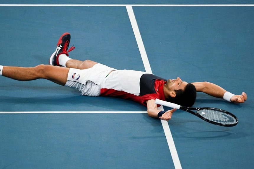 Novak Djokovic falls to the ground after winning his ATP Cup men's singles match against Daniil Medvedev.