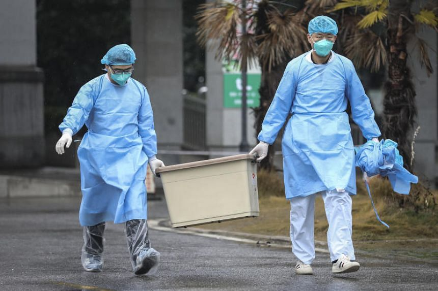 Hospital staff at the south building of the Wuhan Medical Treatment Centre.