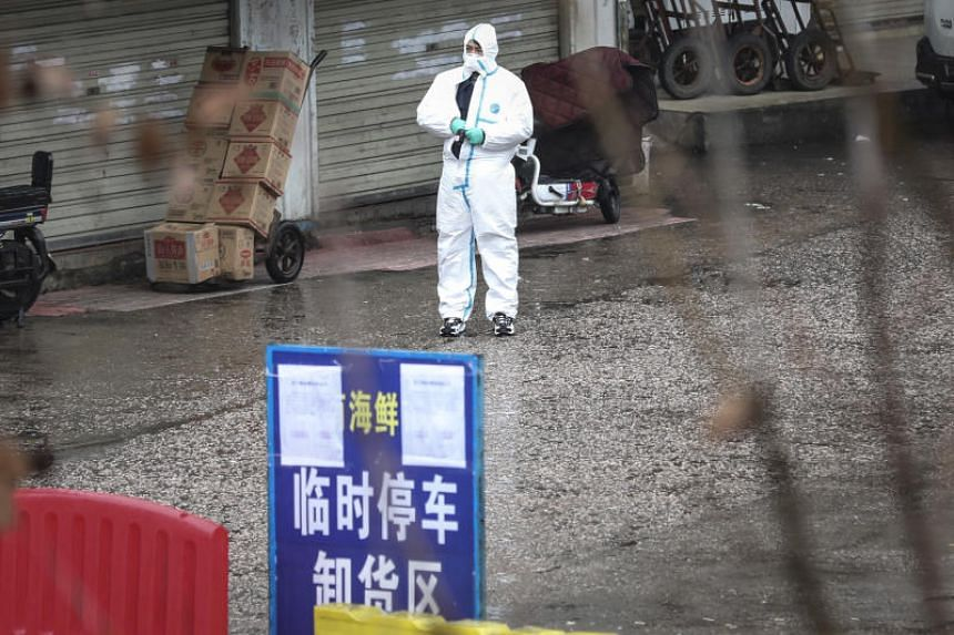 Public health workers at the Wuhan Huanan Seafood Wholesale Market, believed to be the centre of the mysterious pneumonia outbreak. Many of those infected were workers or visitors to the market.