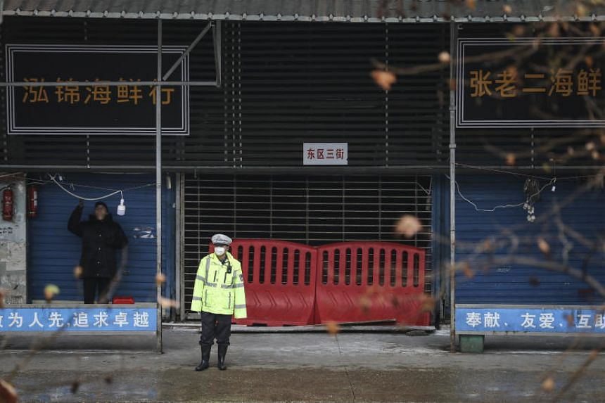 Security staff guarding the shut Wuhan Huanan Seafood Wholesale Market.