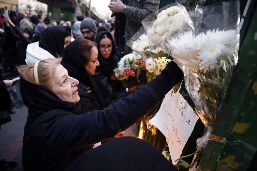 Iranians light candles and hang flowers for victims of the plane crash during a protest in front of Amir Kabir University in Teheran, Jan 11, 2020.