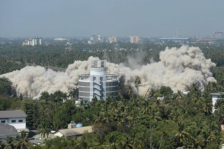 An apartment complex in Kerala's Maradu district being demolished yesterday using controlled implosions, after a court last year ordered its demolition for violating coastal construction regulations. Two buildings were razed yesterday and a remaining