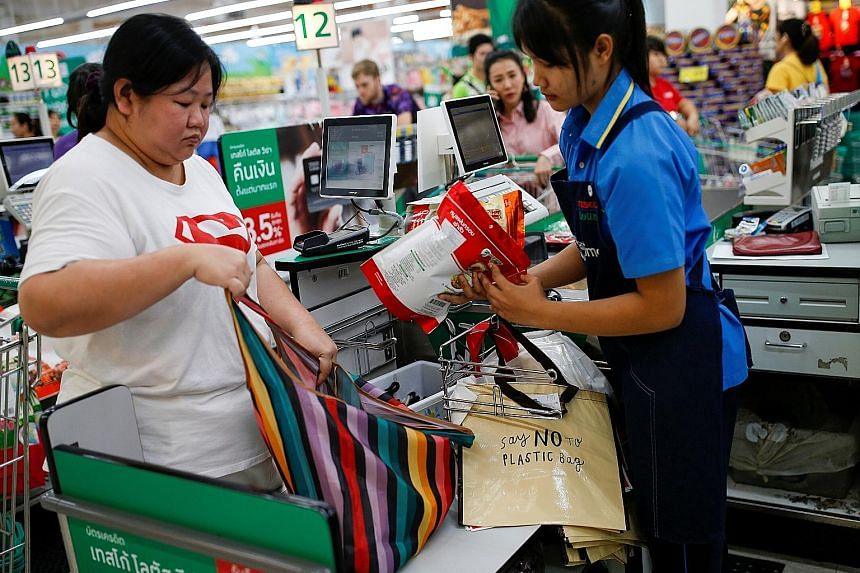 Top left: Banners informing customers about the ban on single-use plastic bags at a shopping mall in Bangkok, as major Thai retailers kicked off the new year with the curbs. Above: A woman using a shopping bag at a shopping centre in Bangkok on Jan 2