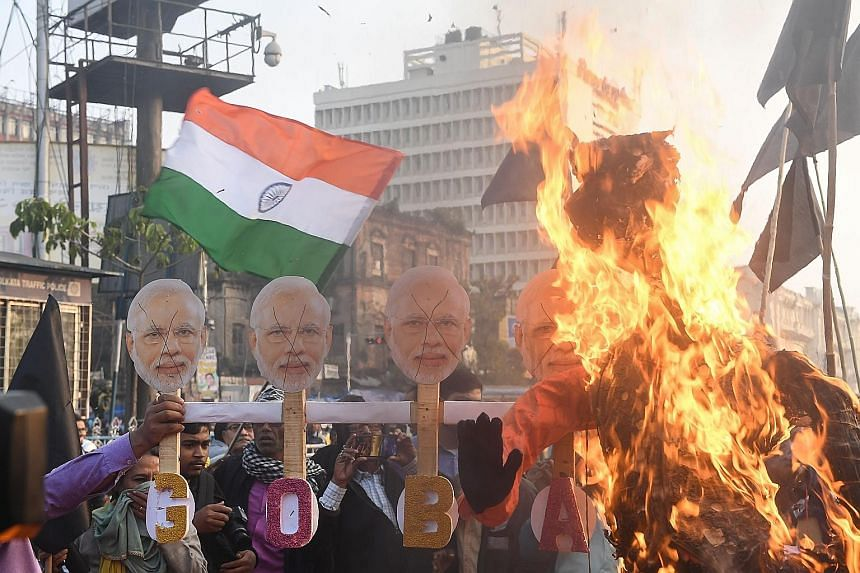 Activists (left) burning masks with the face of India's Prime Minister Narendra Modi, and others (below, left) displaying banners and shouting slogans against Mr Modi as they protested against India's new citizenship law in Kolkata yesterday.