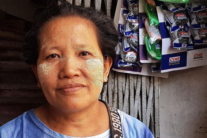 Street vendor San San Oo, a long-time thanaka user, buys the fresh paste from the market and smears it on her cheeks with a brush.