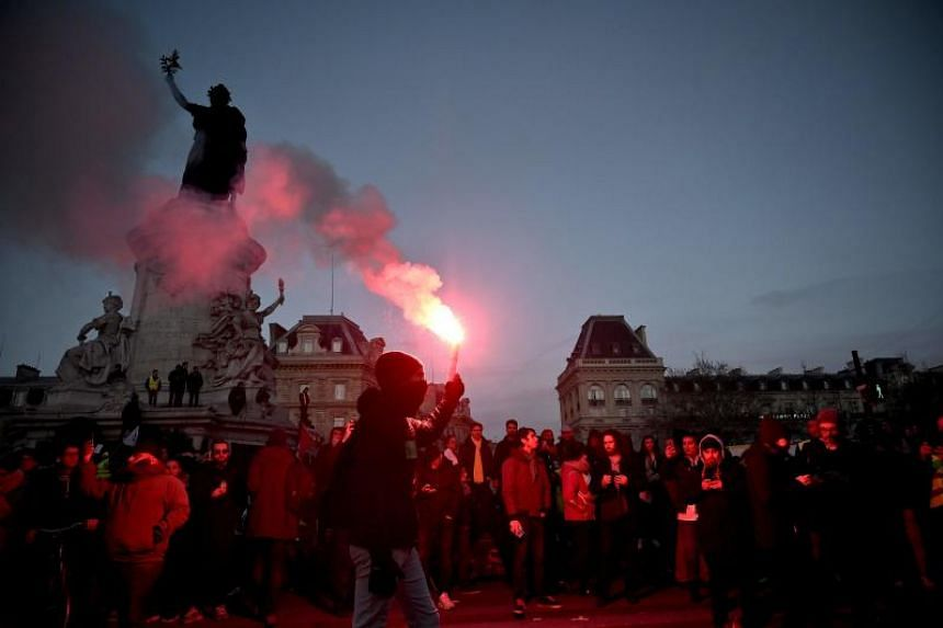 Protesters light flares during a demonstration in Paris, on Jan 11, 2020, as part as a nationwide multi-sector strike against the French government's pensions overhaul.