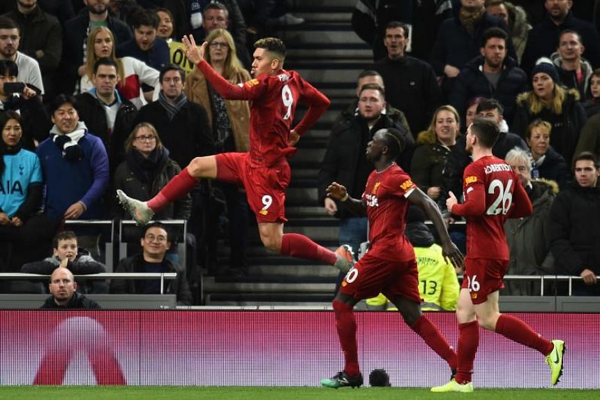 Liverpool midfielder Roberto Firmino (left) celebrates scoring the opening goal during the English Premier League football match against Tottenham Hotspur in London, on Jan 11, 2020.