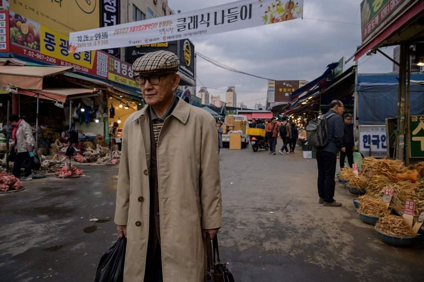 In a photo taken on Oct 28, 2019, a man carries shopping bags as he makes his way through a market in Seoul.