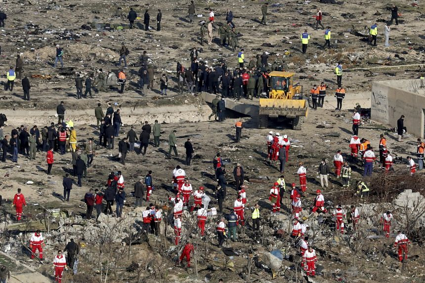 In a photo taken on Jan 9, rescue workers search the scene where a Ukrainian plane crashed in Shahedshahr, Iran.