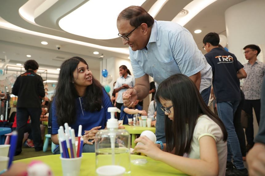 Minister for Communications and Information S. Iswaran chats with volunteer Rithula John (left) and library visitor Zoey Ling during the 1st anniversary of library@harbourfront on Jan 12, 2020.