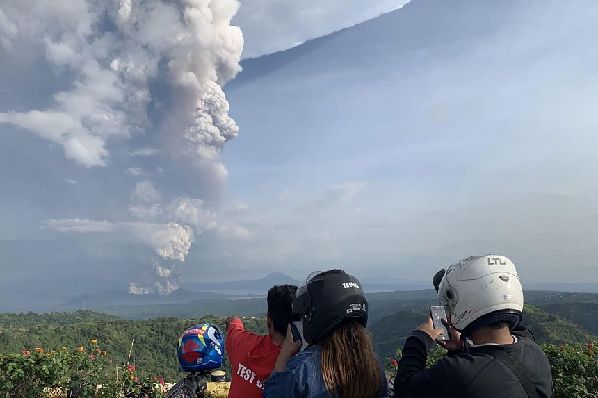People take photos of a phreatic explosion from Taal volcano in Batangas province, on Jan 12, 2020.