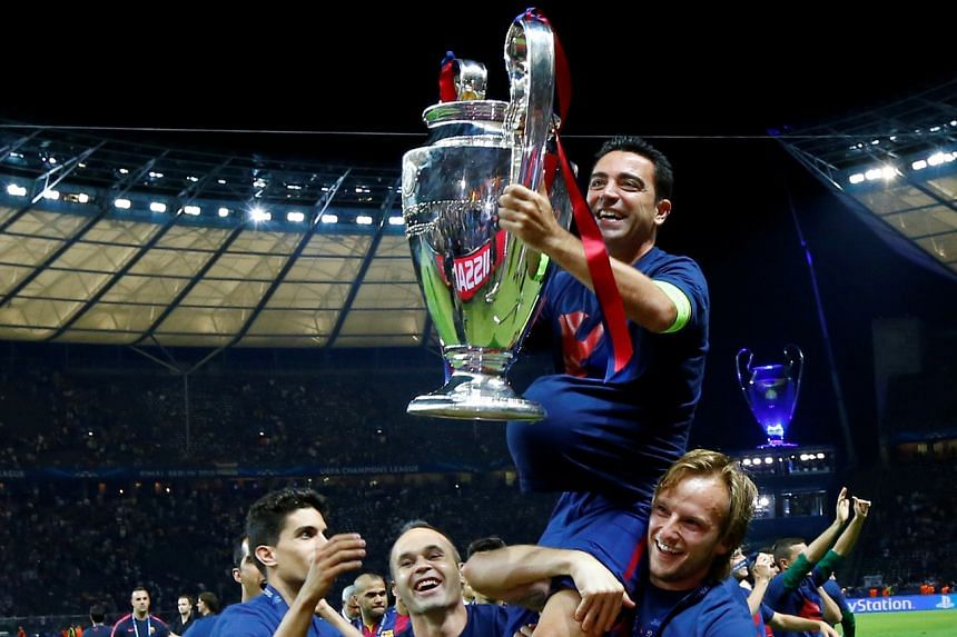 In a photo taken on June 6, 2015, Barcelona's Xavi celebrates with the trophy and teammates after winning the UEFA Champions League.