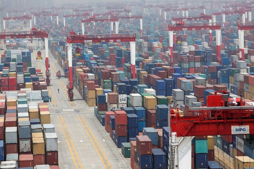 A man walks in a shipping container area in Shanghai on May 11, 2012.