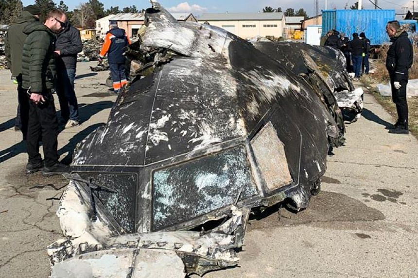 A handout photograph provided by The National Security and Defense Council of Ukraine on Jan 11, 2020, shows people standing and analysing the fragments and remains of the Ukraine International Airlines plane that crashed outside Teheran.