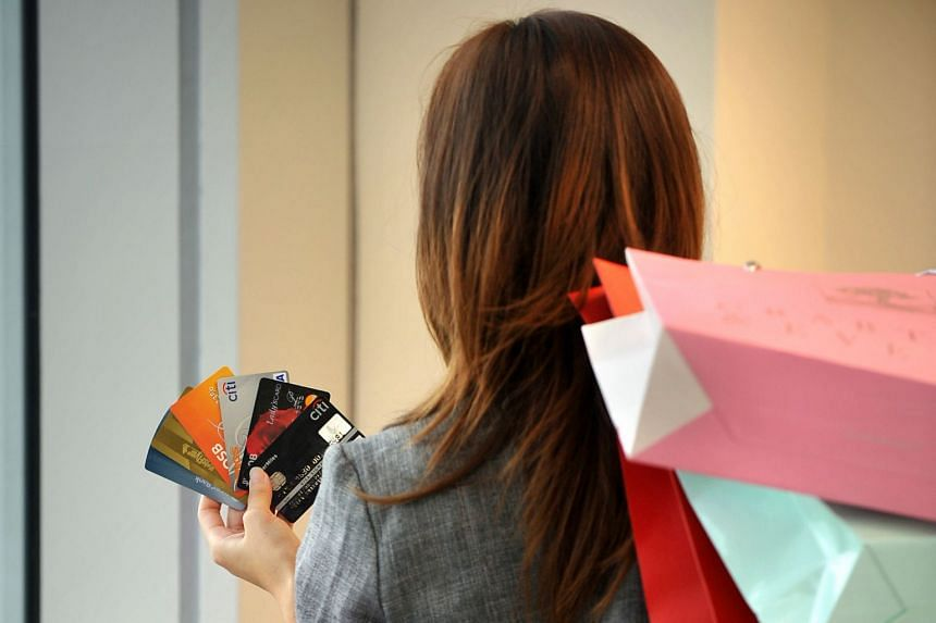 Posed photo of a shopper holding credit cards and shopping bags.