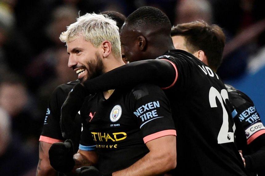 Aguero celebrates scoring City's third goal against Villa with Benjamin Mendy.