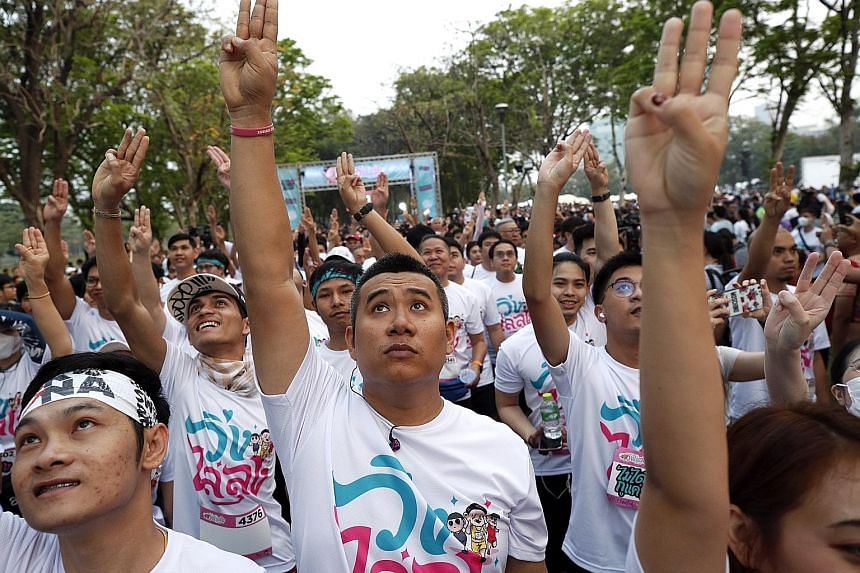 Participants flashing a three-finger salute as they took part in the Run Against Dictatorship event at a public park in Bangkok yesterday.