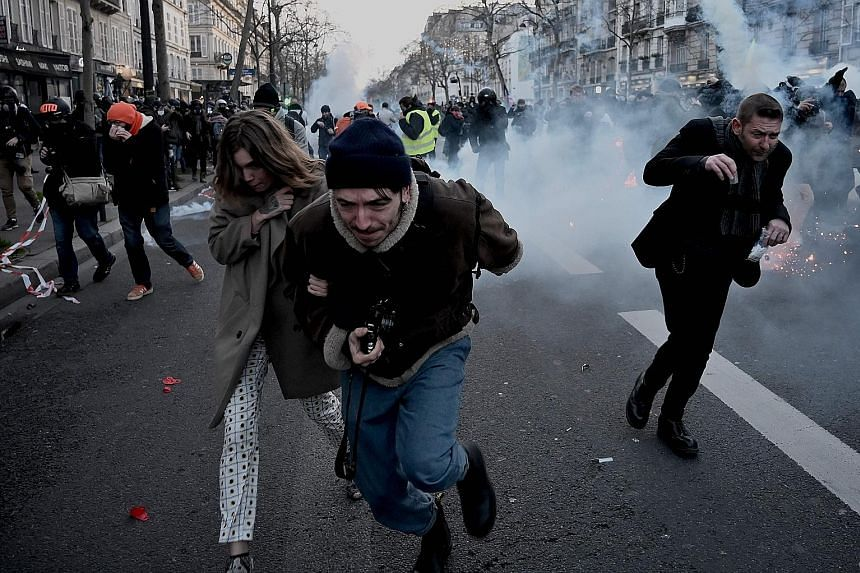 Protesters running away from tear gas during a demonstration last Saturday in Paris, as part as a nationwide multi-sector strike against the French government's move to overhaul the pension system.