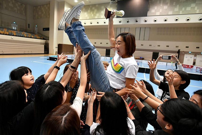 Louise Khng, 37, head coach of the national women's floorball team, being thrown in the air by her players while holding her appreciation trophy during Singapore Floorball Association's appreciation lunch at Our Tampines Hub yesterday. Khng took up t