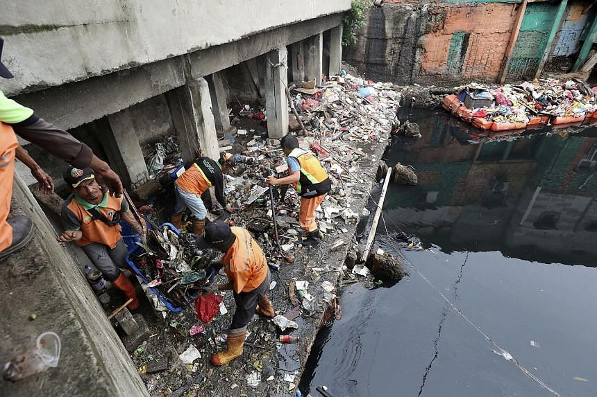 Above: Workers collecting rubbish during a clean-up after floods over the New Year in the Indonesian capital Jakarta. Below: Rescuers evacuating a boy from a flooded area in the capital on Jan 2. PHOTOS: ASSOCIATED PRESS, EPA-EFE