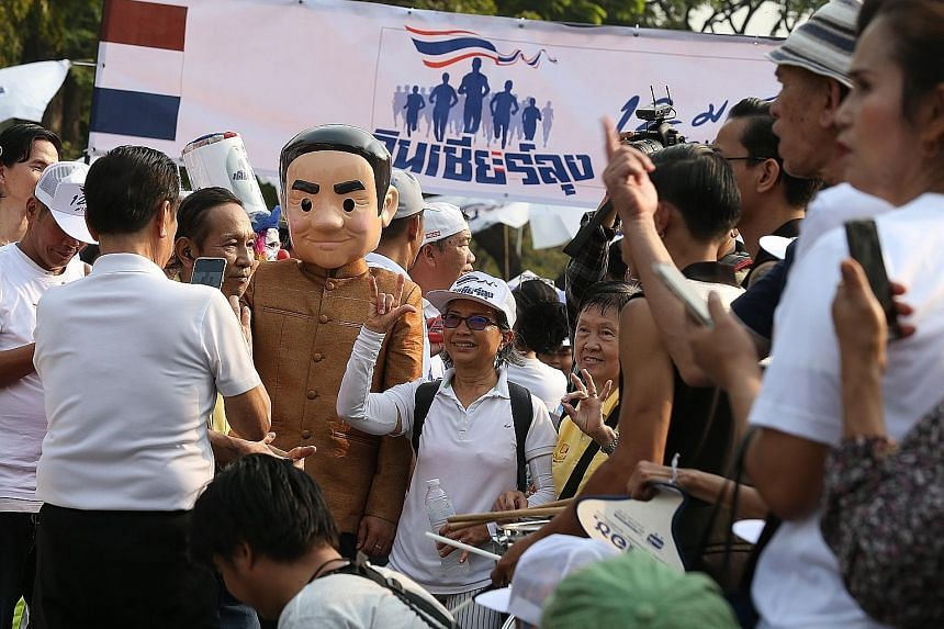 "A supporter of Mr Prayut Chan-o-cha, dressed as the Thai Prime Minister (top), taking part in a ""Walk for Prayut"" event at Lumpini Park in the Thai capital Bangkok yesterday. The rally was held to counter an anti-government event (above) dubbed ""Run"