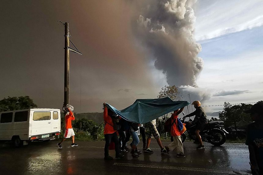 People taking cover under a large plastic sheet as a column of ash spewed from Taal Volcano over Tagaytay city, Philippines, yesterday. Ash fell as far away as Manila, prompting the suspension of flights at the capital's busy international airport. T