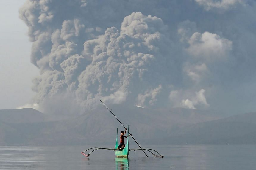 A boy rides an outrigger canoe while the Taal volcano spews ash as seen from Tanauan town in Batangas province, south of Manila, on Jan 13, 2020.