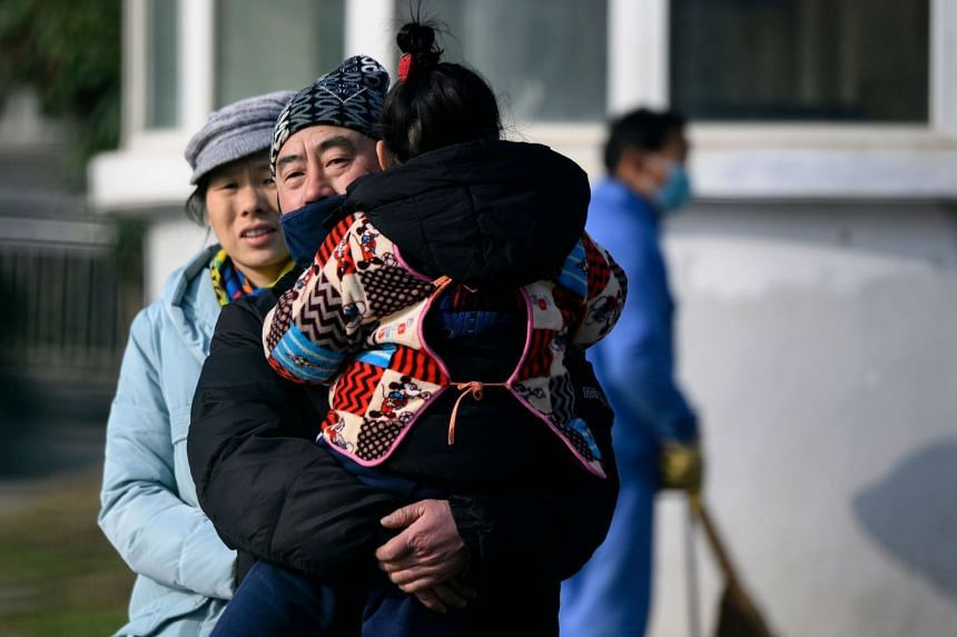A man holding his daughter leaves the Wuhan Medical Treatment Centre in Wuhan, Hubei province, on Jan 12, 2020.