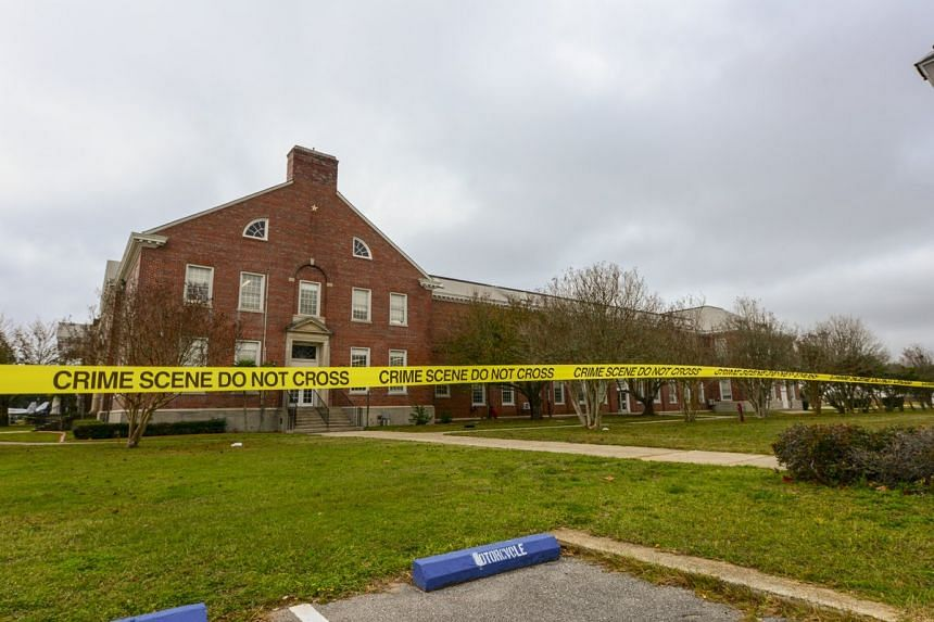 An FBI photo shows police tape stretching across a street near a building after a shooting incident at a naval base in Pensacola, Florida.